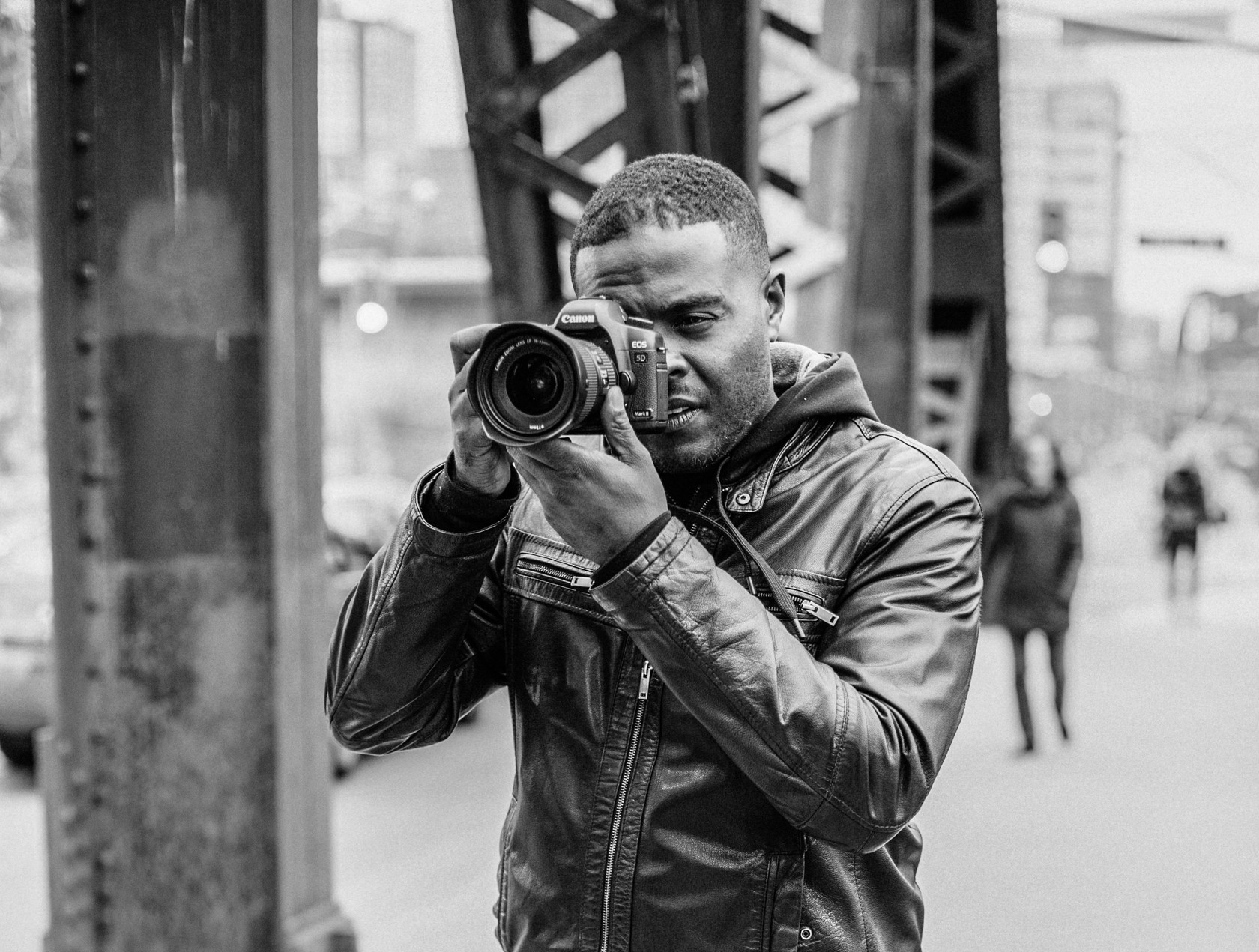 Black and White photo of Derrick Fagan, holding a Canon camera to his left eye, Owner of DF Media Productions a Video Production Company in Toronto, Canada